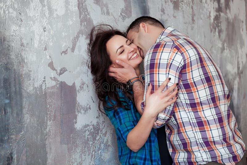 Portret die van mooi jong paar in en vrijetijdskleding die koesteren glimlachen, zich tegen grijze muur bevinden royalty-vrije stock afbeelding