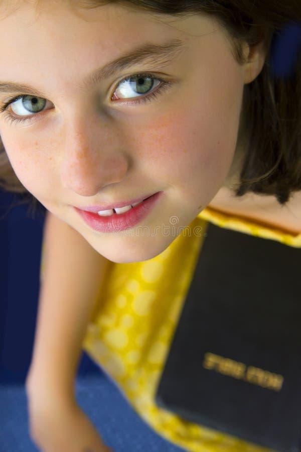 Portret die van mooi meisje Heilige Bijbel houden stock afbeelding