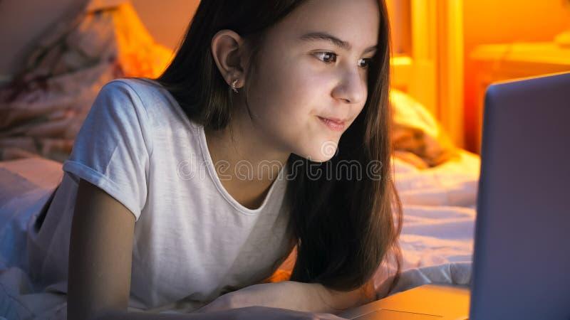 Portret die van mooi meisje op bed en doorbladerend Internet op laptop bij nacht liggen stock afbeeldingen
