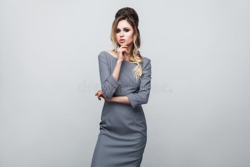 Portret die van mooie aantrekkelijke mannequin in grijze kleding met make-up en kapsel die, en wat betreft haar kin stellen bevin stock afbeeldingen