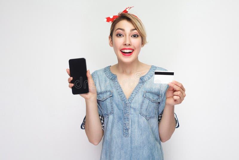 Portret die van mooie gelukkige jonge vrouw in toevallig blauw denimoverhemd met make-up en rode hoofdband die, creditcard houden royalty-vrije stock foto