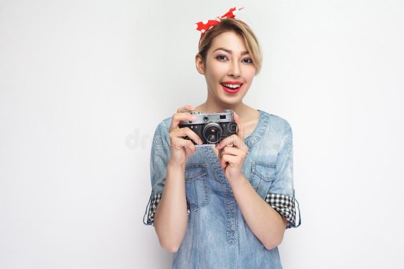 Portret die van mooie jonge bloggervrouw in toevallig blauw denimoverhemd met make-up en rode hoofdband die, retro camera houden  stock afbeeldingen