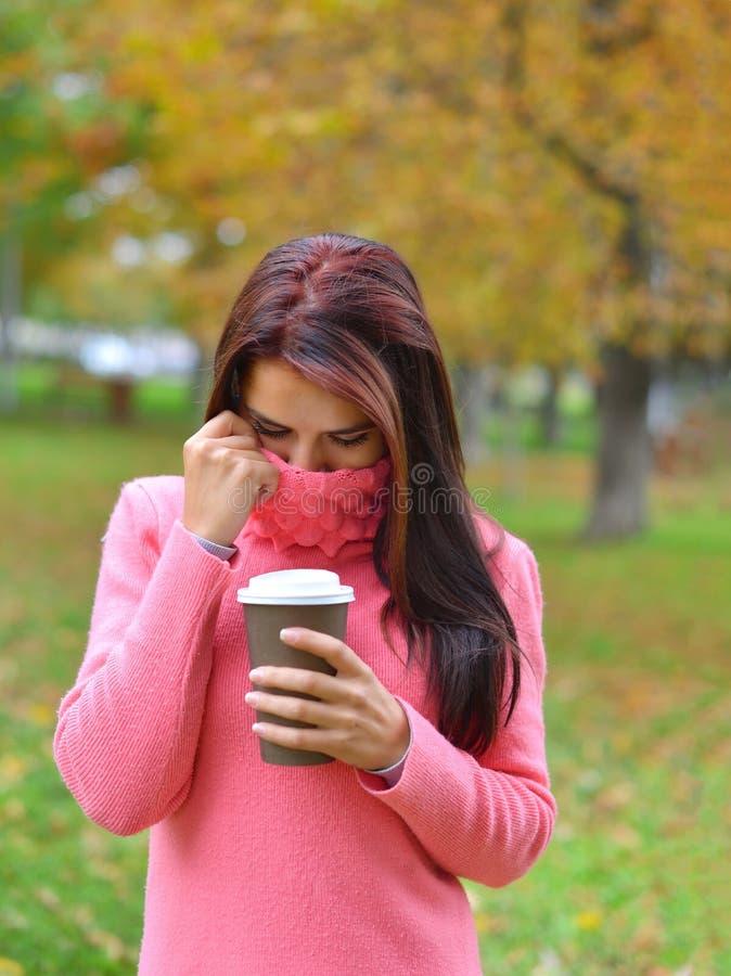Portret die van mooie jonge Kaukasische vrouw, meeneemkoffiekop houden stock afbeelding