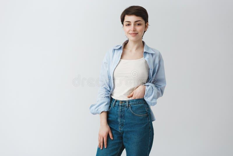Portret die van mooie jonge student die met donker kort haar in toevallige modieuze kleren handen op jeans houden, binnen eruit z royalty-vrije stock foto