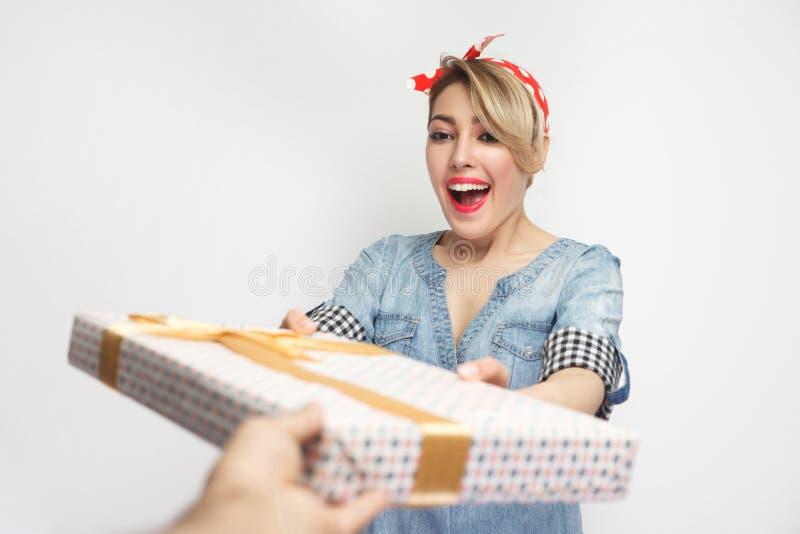 Portret die van mooie jonge vrouw in toevallig blauw denimoverhemd met make-up en rode hoofdband die, gift met gelukkig ontvangen stock afbeeldingen