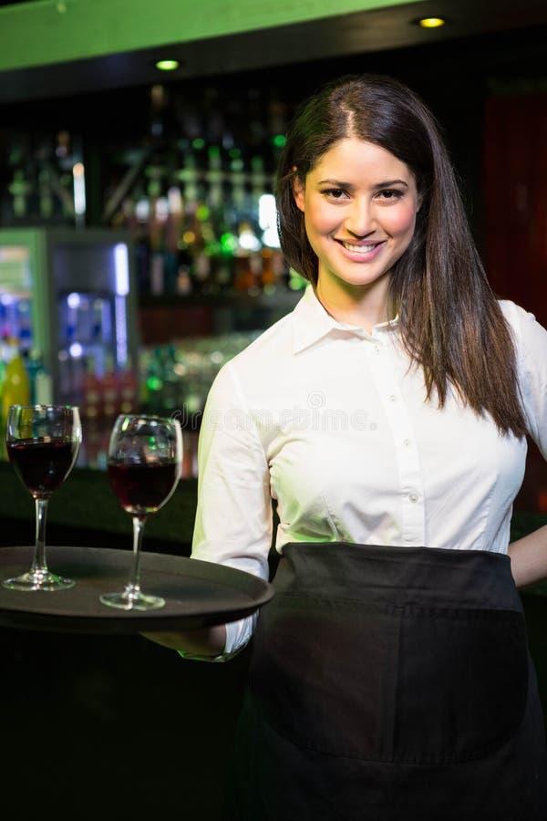 Portret die van mooie serveerster rode wijn dienen royalty-vrije stock foto's