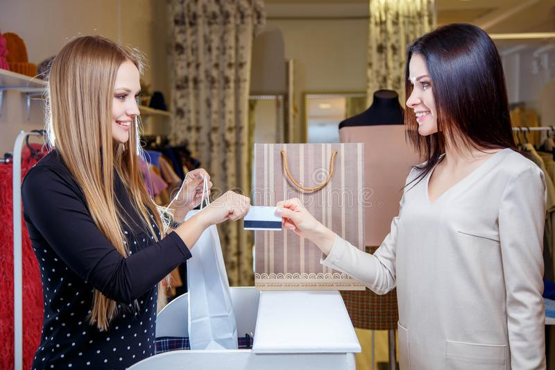 Portret die van mooie vrouw creditcard geven aan winkelmedewerker terwijl het betalen voor haar aankoop royalty-vrije stock fotografie