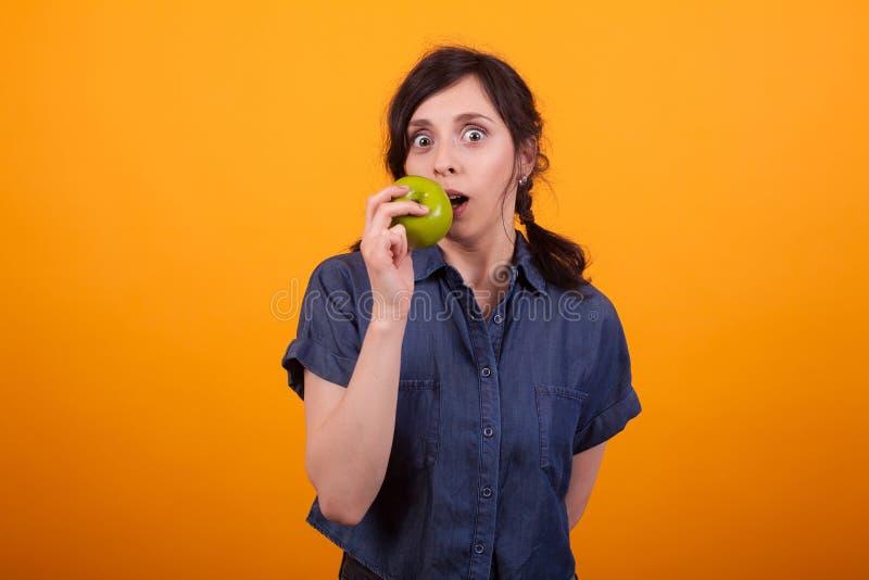 Portret die van mooie vrouw een groene appel bitting en de camera in studio over gele achtergrond bekijken royalty-vrije stock afbeelding