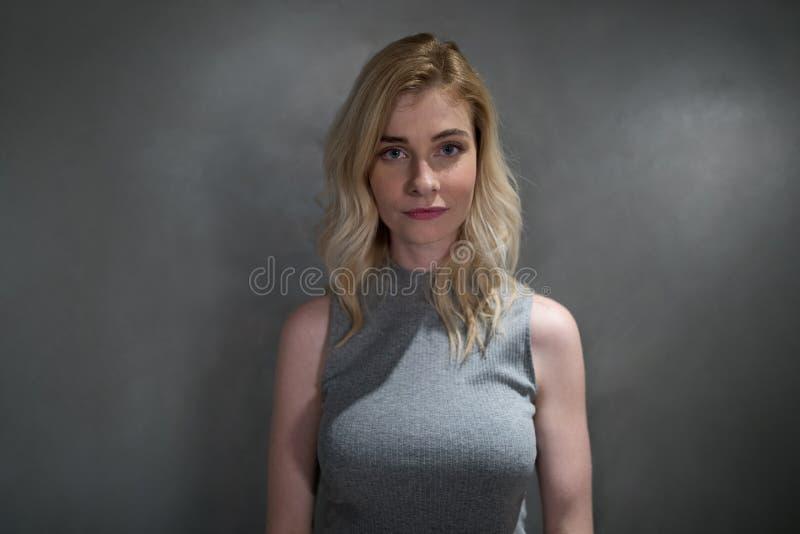 Portret die van mooie vrouw zich tegen grijze achtergrond bevinden stock foto's