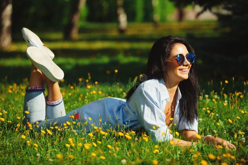 Portret die van mooie vrouw in zonnebril op de zomer groen gras liggen met heldere kleuren Het blije meisje draagt helder stock afbeelding