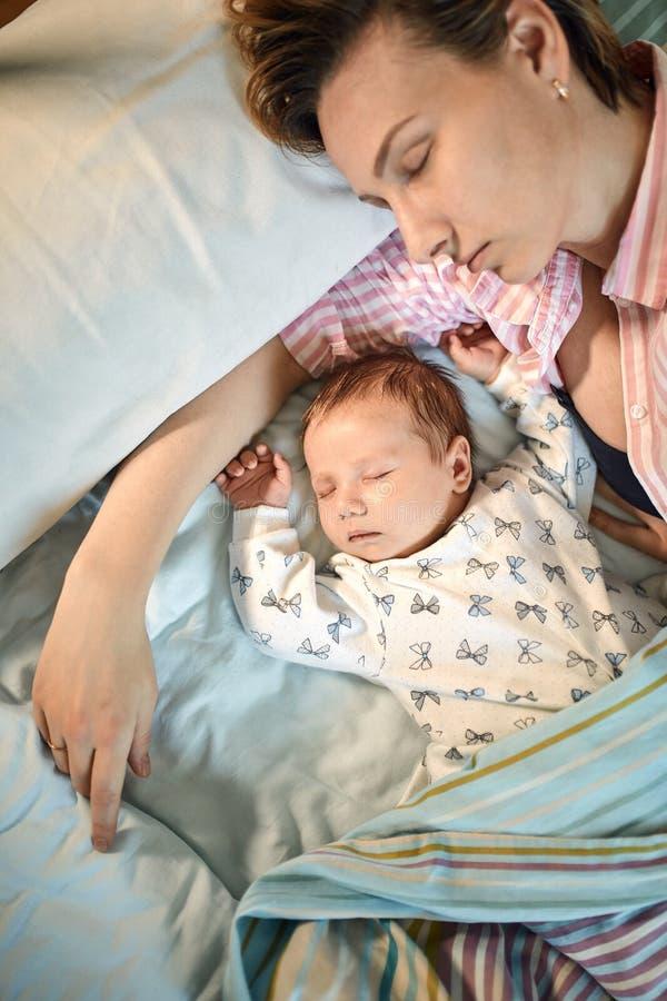 Portret die van pasgeboren baby en moederslaap op bed, samen rusten royalty-vrije stock fotografie