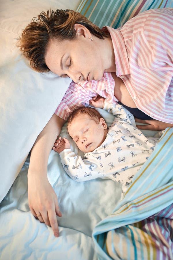 Portret die van pasgeboren baby en moederslaap op bed, samen rusten stock afbeeldingen