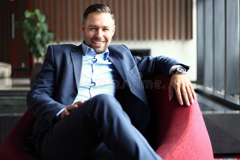 Portret die van positieve jonge zakenmanzitting in een modern collectief milieu, de camera bekijken stock afbeeldingen