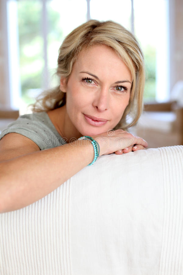 Portret die van rijpe vrouw op bank liggen royalty-vrije stock afbeelding
