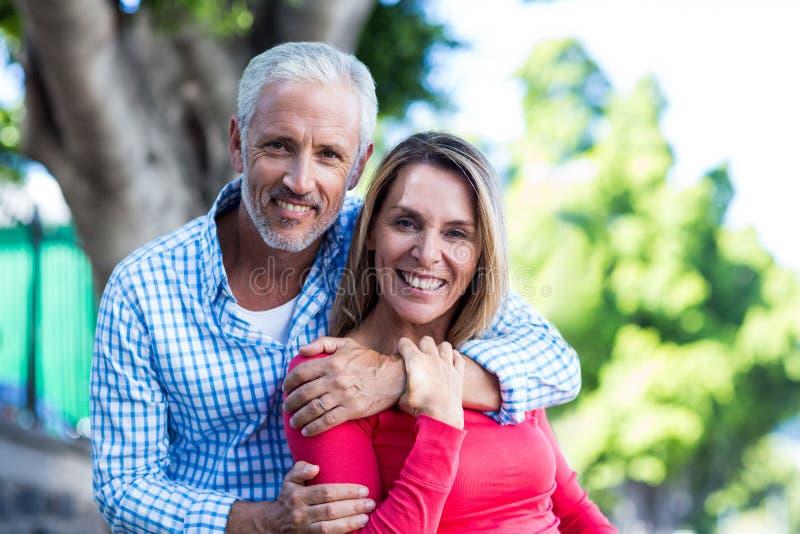 Portret die van romantisch paar zich tegen boom bevinden royalty-vrije stock fotografie