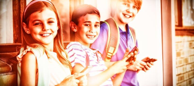 Portret die van schooljonge geitjes mobiele telefoon in gang met behulp van stock foto