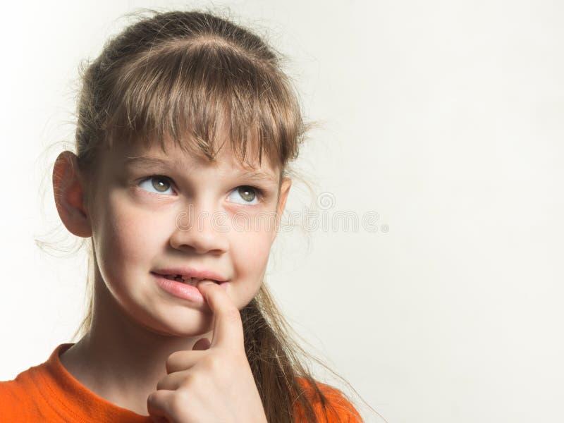 Portret die van schuw meisje met een vinger in haar mond, omhoog zorgvuldig eruit zien royalty-vrije stock fotografie