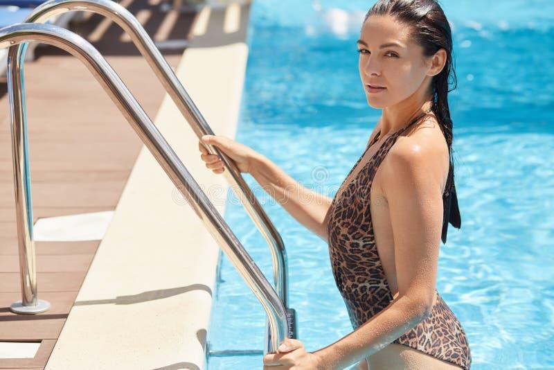 Portret die van sexy aantrekkelijk brunette, op strakke leuningen houden, komend uit zwembad door treden, die het zwemmen hebben royalty-vrije stock fotografie