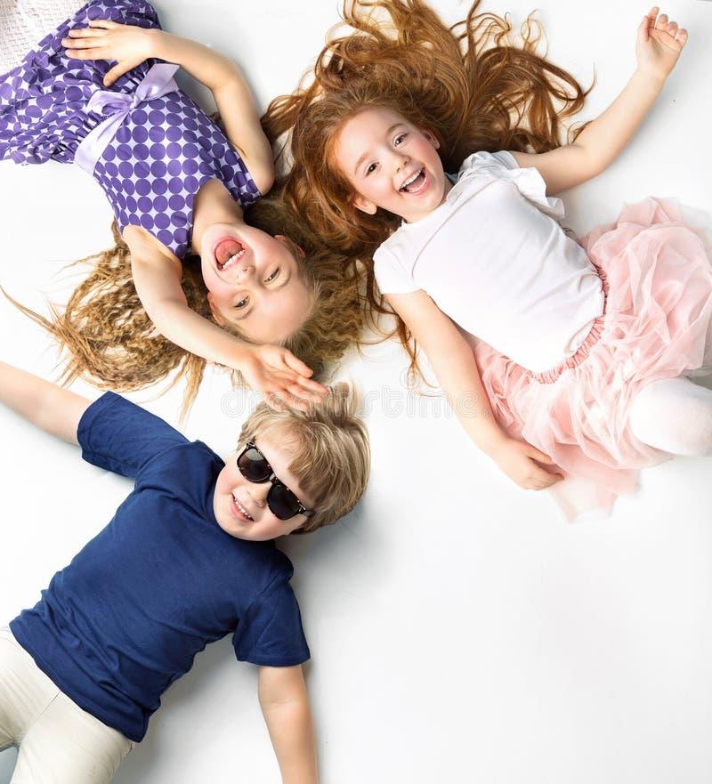Portret die van siblings op een witte achtergrond liggen royalty-vrije stock foto