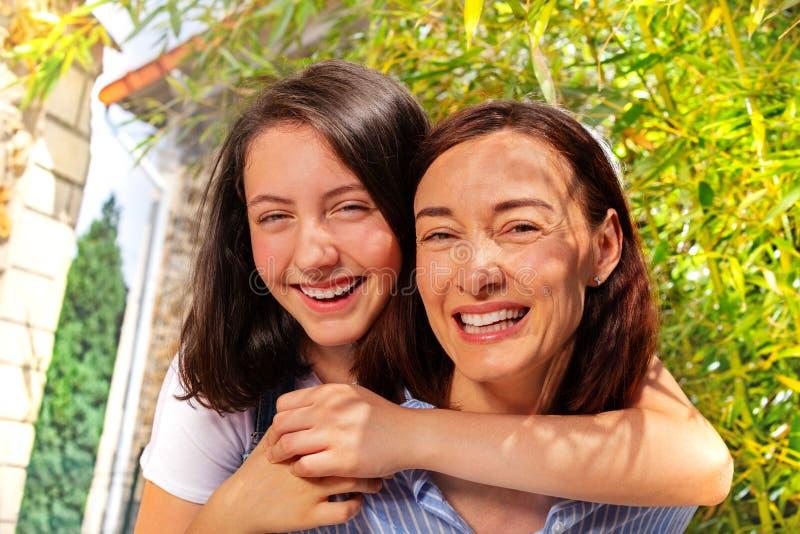 Portret die van tiener haar moeder omhelzen stock foto's