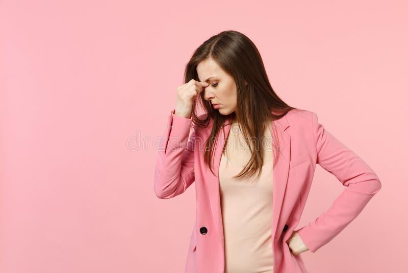 Portret die van vermoeide verstoorde jonge vrouw die jasje dragen die hand op neus zetten, ogen het houden sloot geïsoleerd op pa royalty-vrije stock afbeelding