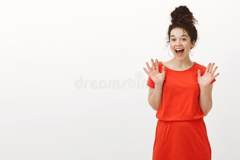 Portret die van verrast opgewonden mooi wijfje met krullend haar in toevallige rode kleding, palmen opheffen en gillen van stock foto