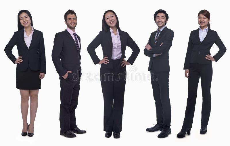 Portret die van vijf jonge glimlachende onderneemsters en jonge zakenlieden, camera, studioschot bekijken stock foto