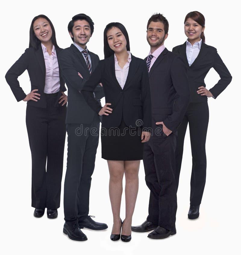 Portret die van vijf jonge glimlachende onderneemsters en jonge zakenlieden, camera, studioschot bekijken stock afbeelding