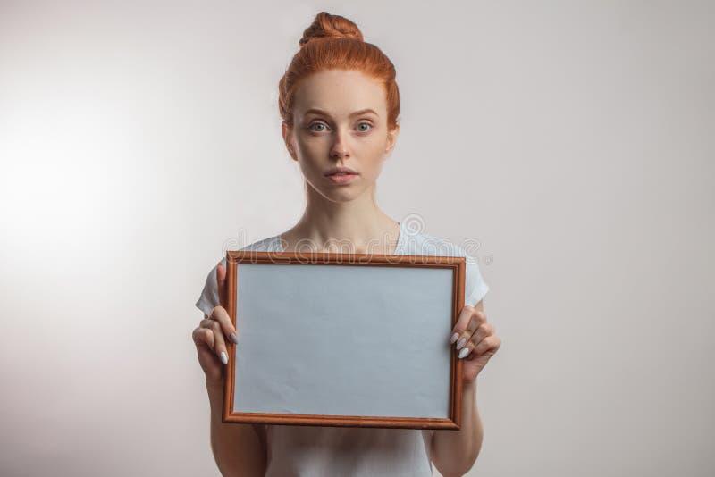 Portret die van vrolijk roodharigemeisje met haarbroodje en sproeten leeg houten kader houden stock foto's