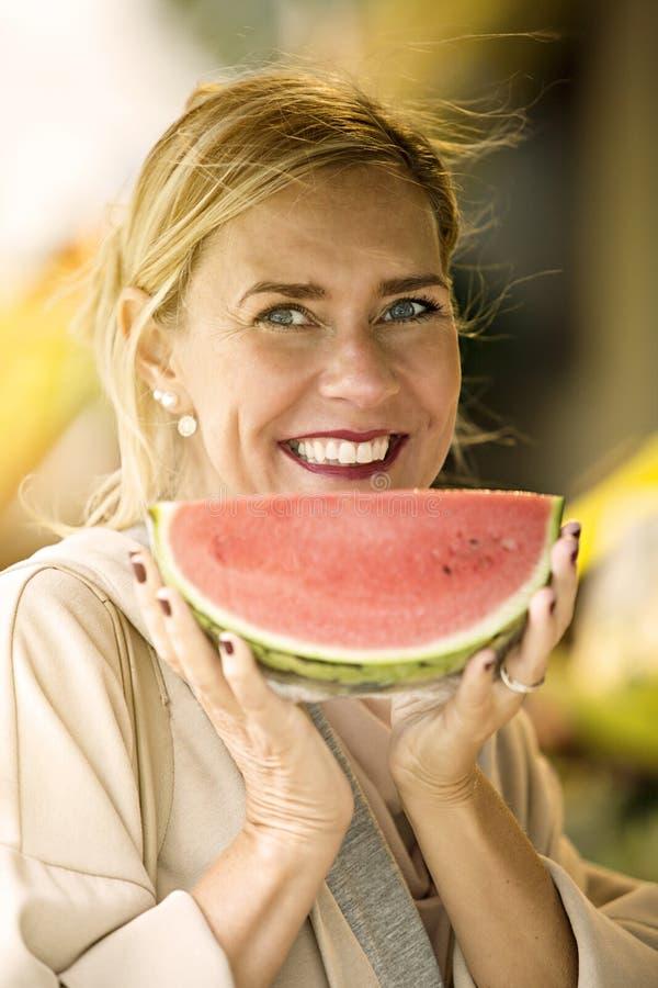 Portret die van vrouw een meloen houden stock foto