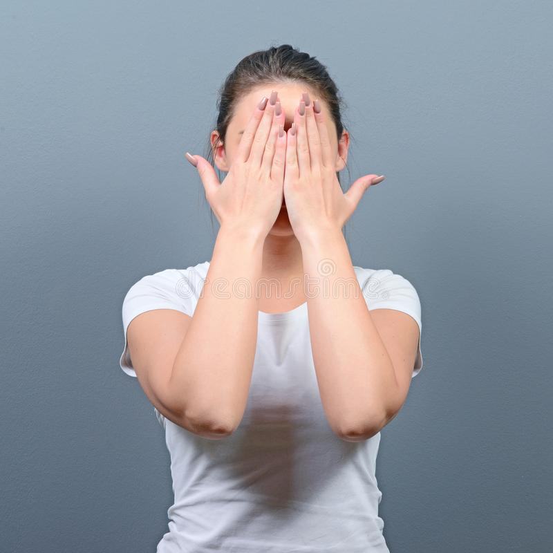 Portret die van vrouw haar gezicht met beide handen verbergen tegen grijze achtergrond stock fotografie