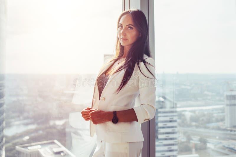 Portret die van vrouw zich dichtbij het venster in bureau bevinden die camera bekijken stock fotografie