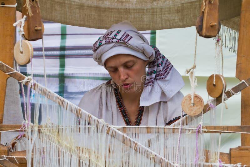 Portret die van vrouwenwever het werken bij oud weefgetouw, tapijt maken royalty-vrije stock fotografie
