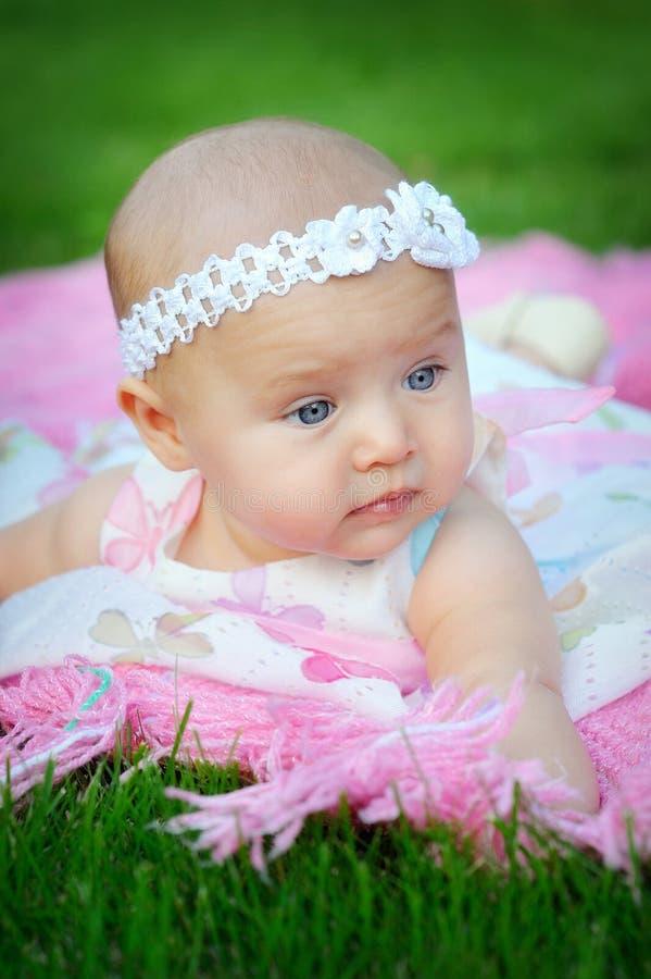 Portret die van weinig leuk babymeisje in het park en een bandag liggen royalty-vrije stock fotografie