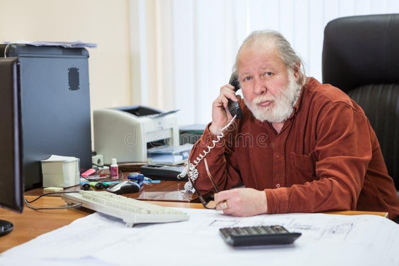 Portret die van witte gebaarde hogere zakenman die telefoon met behulp van, aan somebody roepen terwijl het werken in bureau royalty-vrije stock fotografie