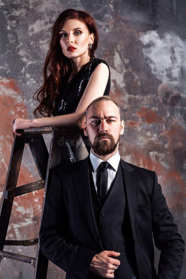 Portret die van zakenman bevinden zich dichtbij steplader en camera met gembervrouw status op oude trapladder bekijken stock foto's