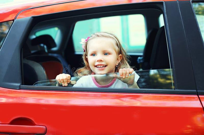 Portret die weinig kindzitting in rode auto glimlachen stock afbeeldingen