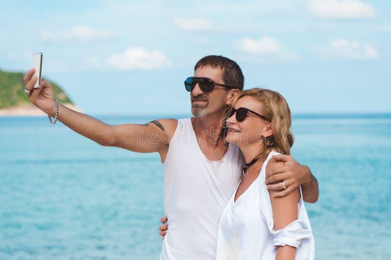 Portret dojrzała uśmiechnięta para bierze selfie przy plażą obrazy royalty free