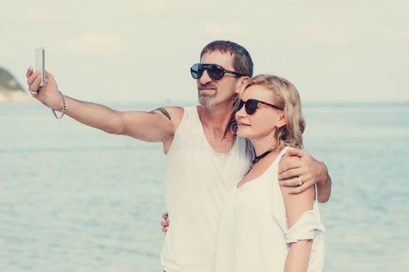 Portret dojrzała uśmiechnięta para bierze selfie przy plażą obraz stock