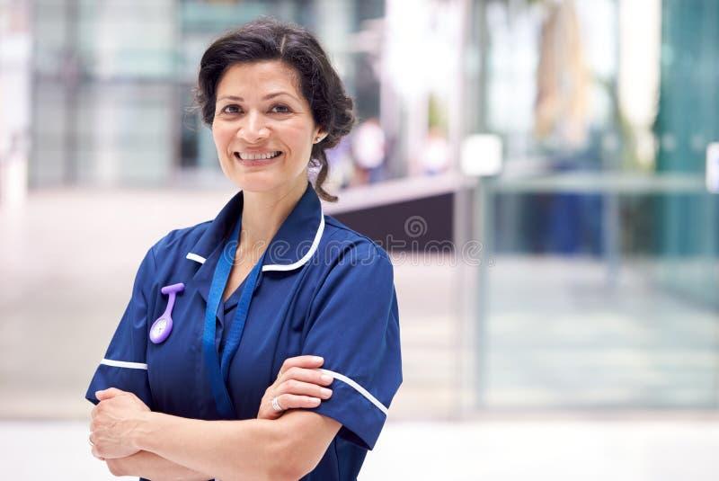 Portret Dojrzałej Pielęgniarki Noszącej Jednolitą Stolicę W Nowoczesnym Budynku Szpitalnym zdjęcia stock