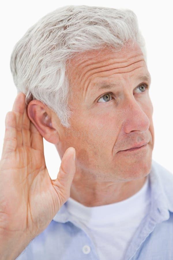 Portret dojrzały mężczyzna daje jego ucho obraz stock