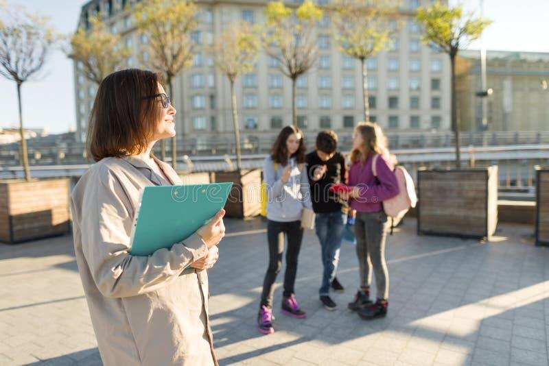 Portret dojrzały uśmiechnięty żeński nauczyciel w szkłach z schowkiem, outdor z grupą nastolatków ucznie obraz stock
