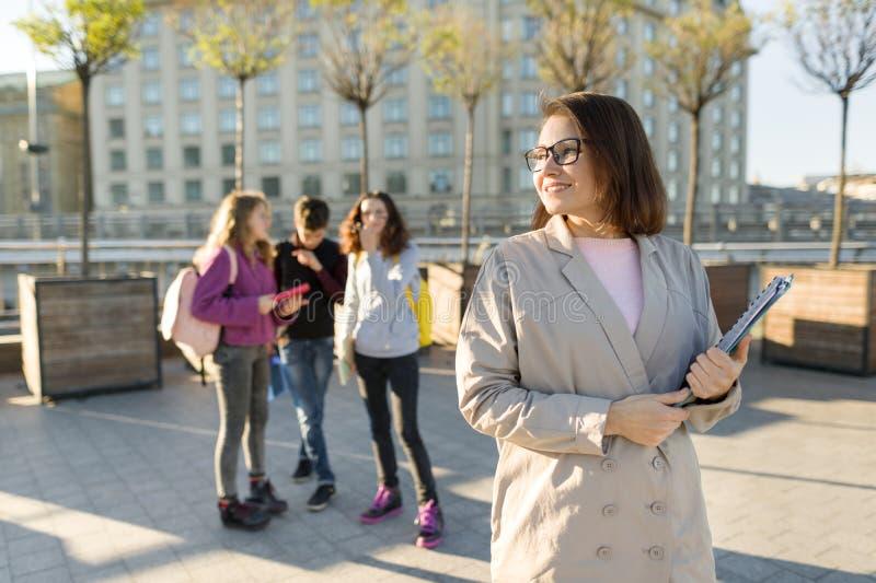 Portret dojrzały uśmiechnięty żeński nauczyciel w szkłach z schowkiem, outdor z grupą nastolatków ucznie zdjęcia royalty free