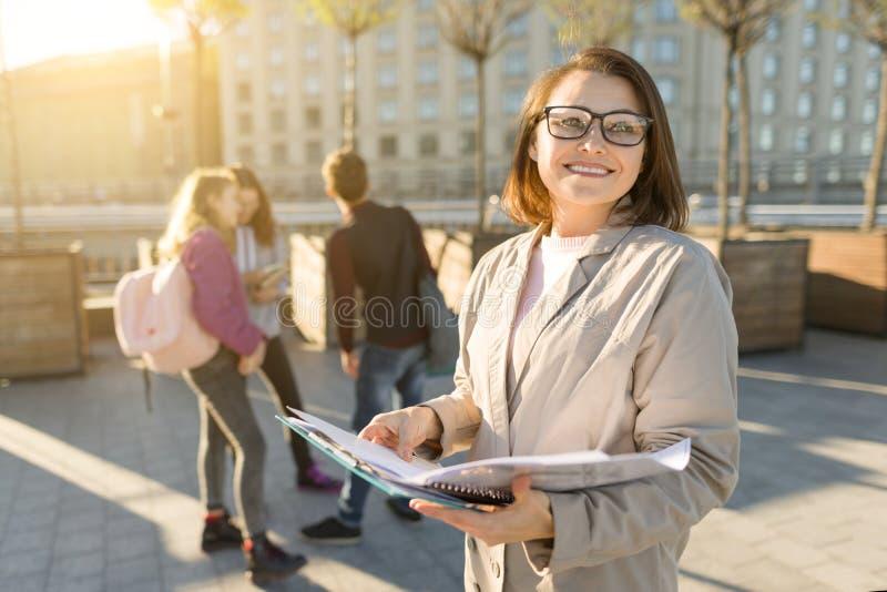 Portret dojrzały uśmiechnięty żeński nauczyciel w szkłach z schowkiem, outdor z grupą nastolatków ucznie obrazy stock