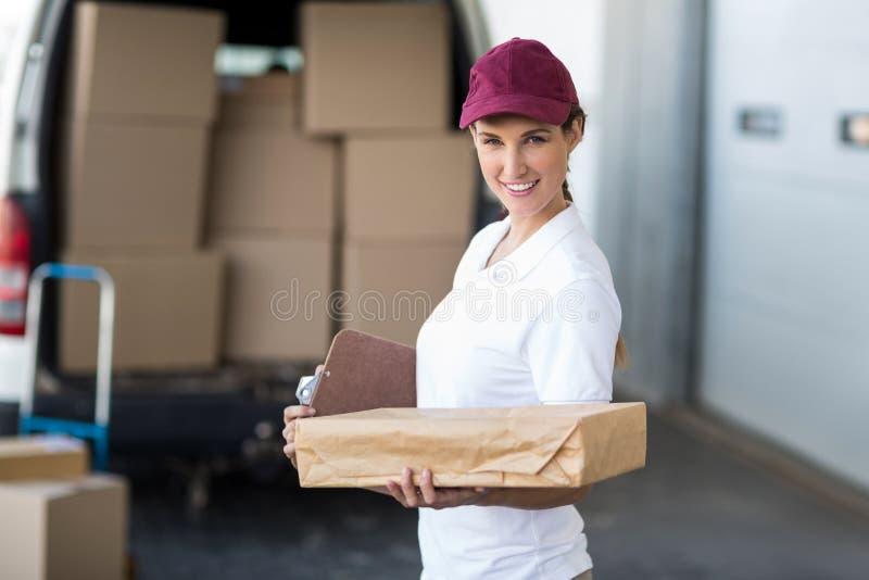 Portret doręczeniowa kobieta trzyma karton i ono uśmiecha się kamera fotografia stock
