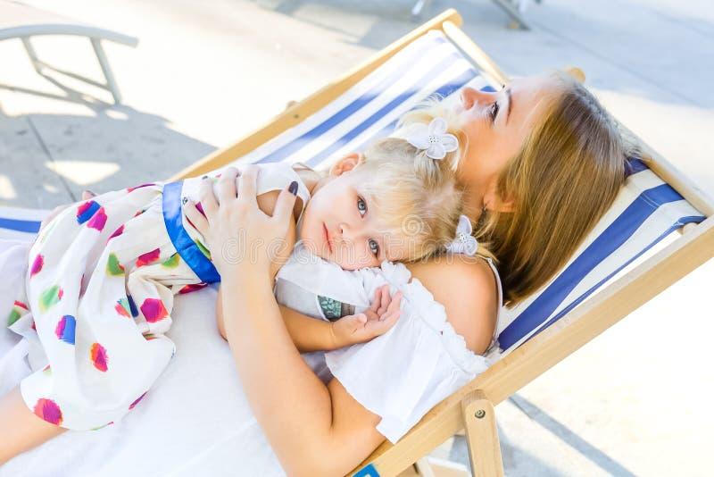 Portret dorable blondy dziewczynka kłaść na jej macierzystym obsiadaniu w deckchair w miasto parka rekreacyjnym terenie w sukni,  zdjęcia stock