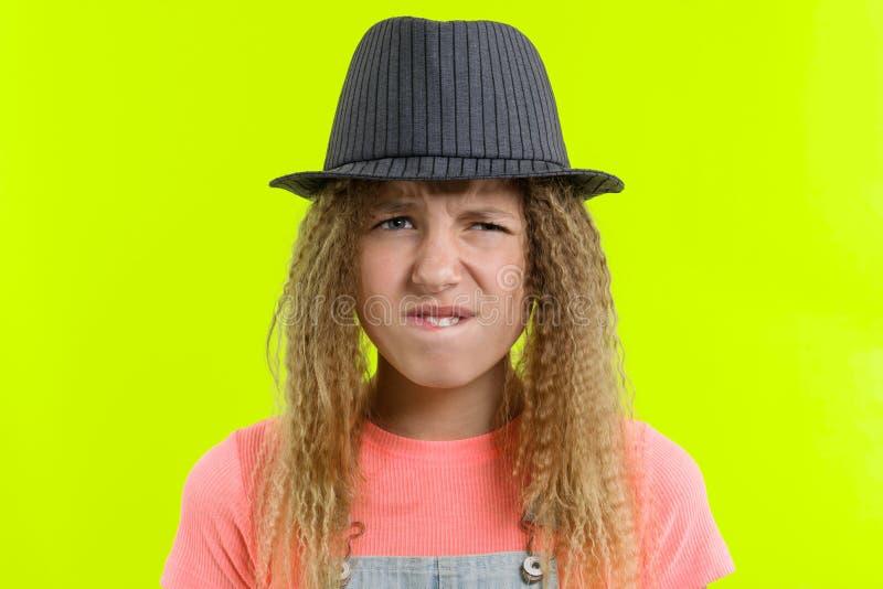 Portret dosyć śmieszna nastoletnia dziewczyna z zadumaną twarzą, blondynki dziewczyna z kędzierzawym włosy w kapeluszu z rozważny obraz royalty free