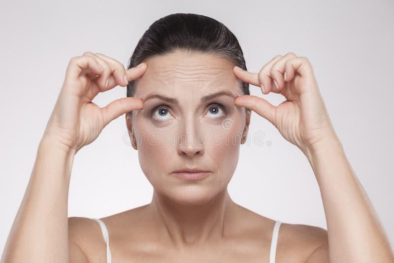 Portret dosyć, czarujący, atrakcyjna w średnim wieku kobieta sprawdza zmarszczenia na jej czole z doskonalić twarzy skórą, trzyma zdjęcia royalty free