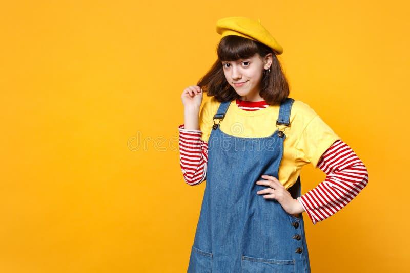 Portret dosyć jaskrawy dziewczyna nastolatek trzyma włosy odizolowywający na kolor żółty ścianie w francuskich bereta i drelichu  fotografia stock