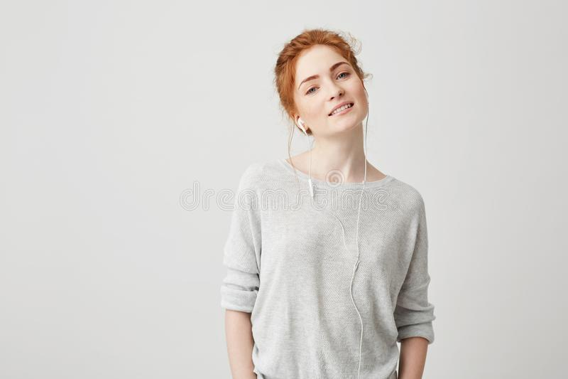 Portret dosyć skwaśniała dziewczyna słucha muzyka w hełmofonach ono uśmiecha się patrzejący kamerę nad białym tłem obrazy royalty free